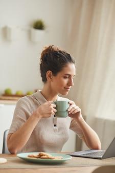 Junge frau, die am tisch sitzt und kaffee trinkt, während laptop zu hause verwendet wird