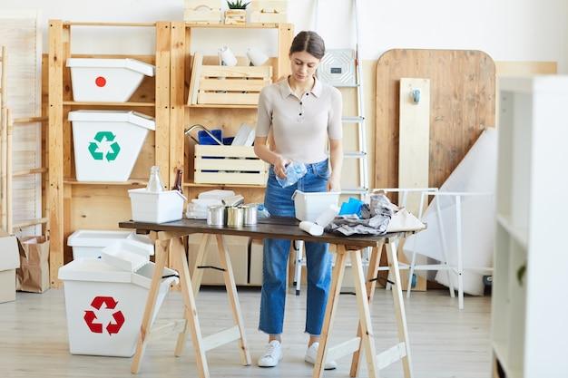 Junge frau, die am tisch steht und den abfall in die plastikbehälter im lager recycelt