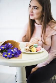 Junge frau, die am weißen tisch mit blumenblumenstrauß und -makronen auf platte sitzt