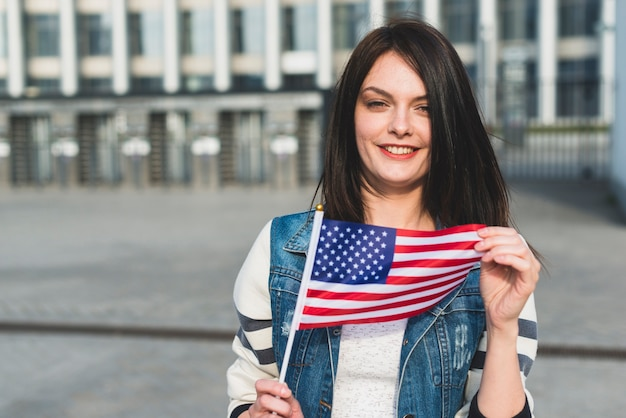 Junge frau, die amerikanische flagge am unabhängigkeitstag hält