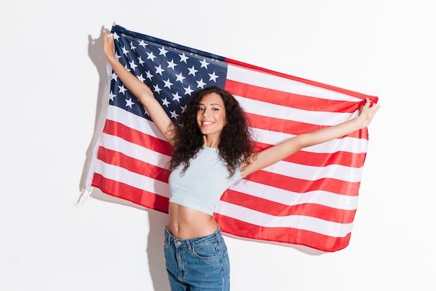 Junge frau, die amerikanische flagge lokalisiert hält