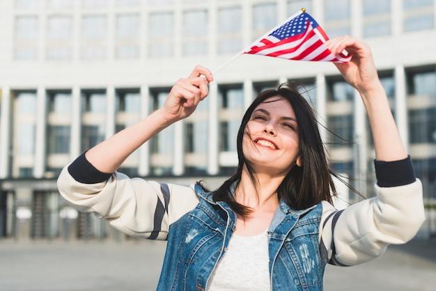 Junge frau, die amerikanische flagge über kopf am vierten juli hält