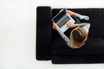 Junge Frau, die an dem Laptop, sitzend auf schwarzem gemütlichem Sofa, weißer Boden arbeitet.