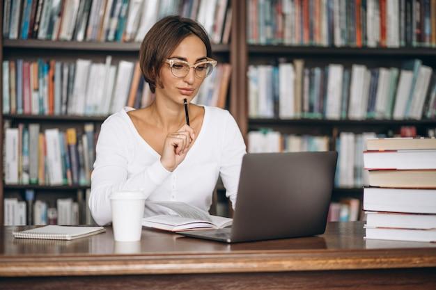 Junge frau, die an der bibliothek unter verwendung der bücher und des computers sitzt