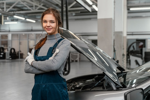 Junge frau, die an einem autoservice arbeitet