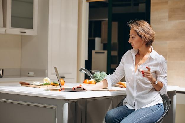 Junge frau, die an einem computer an der küche arbeitet