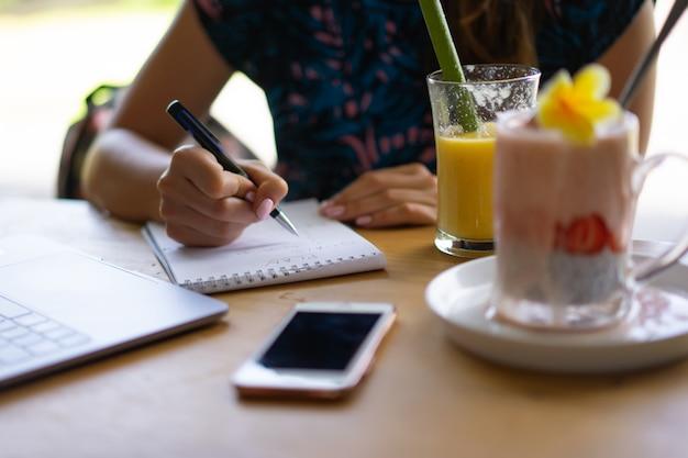 Junge frau, die an einem laptop, einem gesunden frühstück mit chia samen und saft arbeitet.