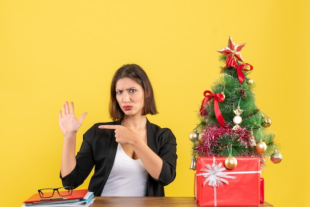 Junge frau, die an einem tisch sitzt und ihre hand im anzug nahe geschmücktem weihnachtsbaum im büro auf gelb zeigt