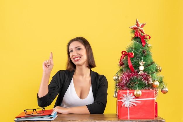 Junge frau, die an einem tisch sitzt und im anzug nahe geschmücktem weihnachtsbaum im büro auf gelb zeigt