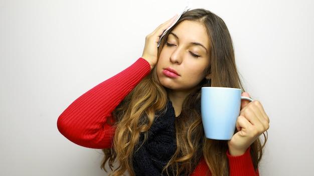 Junge frau, die an erkältung oder grippe erkrankt ist, trinkt etwas heißes