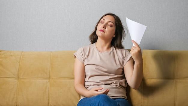 Junge frau, die an hitze leidet, fächert sich mit einem blatt papier auf, während sie auf der couch sitzt.