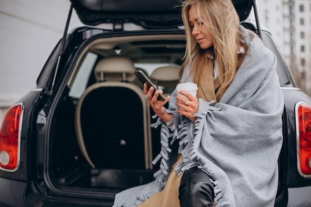 Junge frau, die an ihrem auto steht und kaffee trinkt