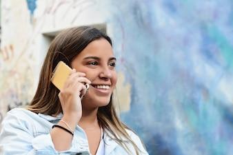 Junge Frau, die an ihrem Handy spricht.