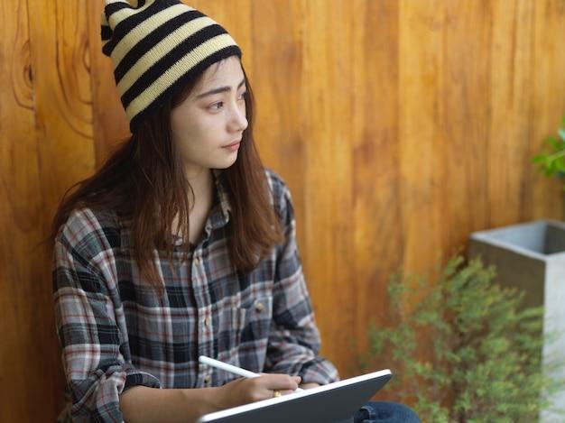 Junge frau, die an ihrem projekt mit tablette arbeitet, während sie über die idee nachdenkt