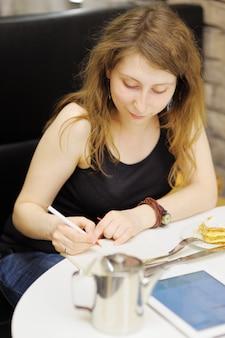 Junge frau, die an ihrem tablet-computer in einem café arbeitet oder studiert