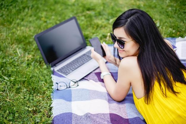 Junge frau, die an laptop im im freien arbeitet