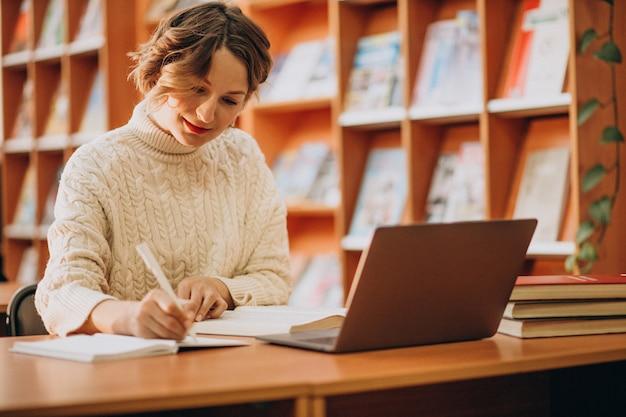 Junge frau, die an laptop in einer bibliothek arbeitet