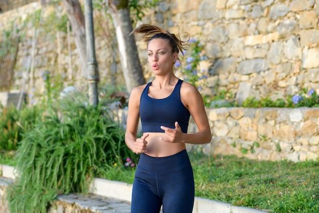 Junge frau, die an ort und stelle während ihres herz-kreislauf-trainings im freien im garten in einem gesundheits- und fitnesskonzept in einer nahen dreiviertel-körperansicht joggt