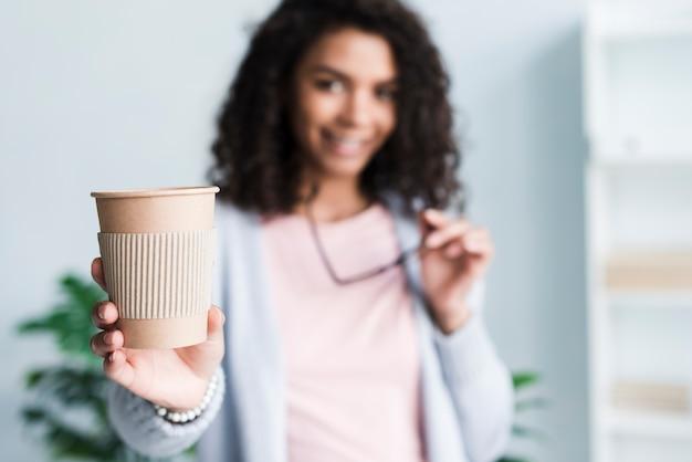 Junge frau, die anbietet, kaffee bei der arbeit zu trinken