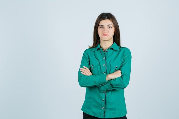 Junge frau, die arme verschränkt, während sie die lippen im grünen hemd krümmt und unzufrieden schaut, vorderansicht.