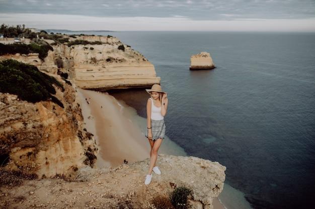 Junge frau, die atemberaubende aussicht bewundert, während sie auf sehr rand der bergspitze steht