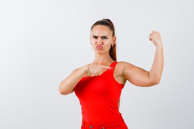 Junge frau, die auf armmuskeln im roten trägershirt, in der hose und in der selbstbewussten vorderansicht zeigt.