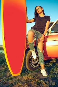 Junge frau, die auf auto mit surfbrett sitzt