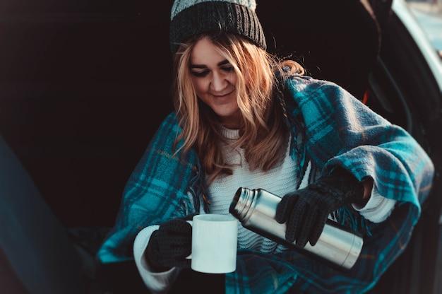 Junge frau, die auf autokofferraum mit kaffeetassen und thermoskanne im winterfeld sitzt.