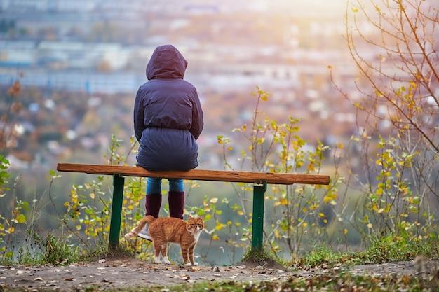 Junge frau, die auf bank im herbststadtpark sitzt