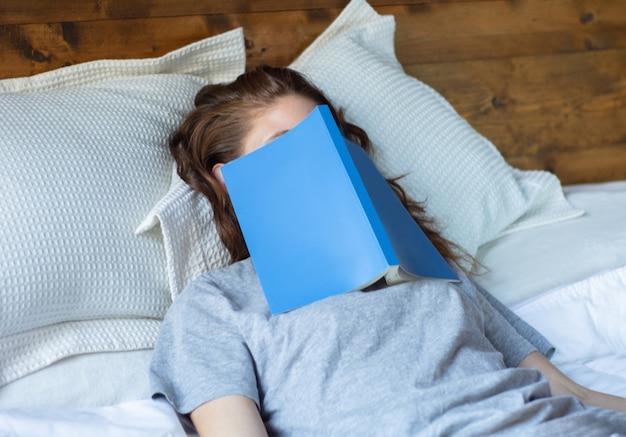 Junge frau, die auf bett mit buch schläft