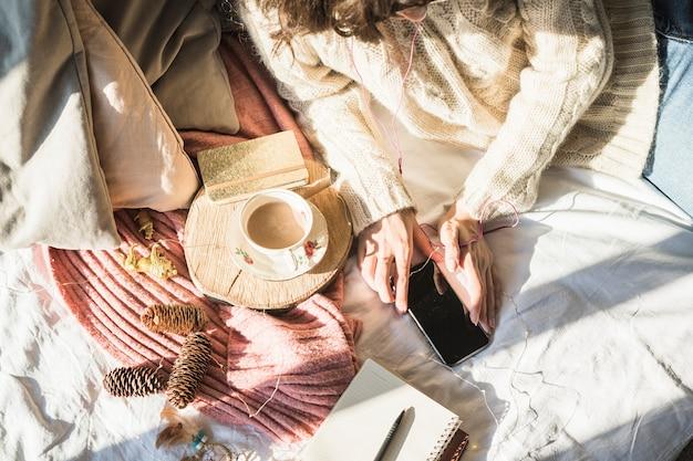 Junge frau, die auf bett mit tasse kaffee liegt und smartphone verwendet