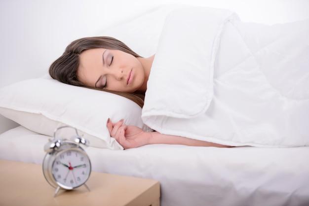 Junge frau, die auf bett mit wecker schläft