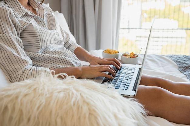 Junge frau, die auf bett unter verwendung des laptops mit gesundem frühstück sitzt
