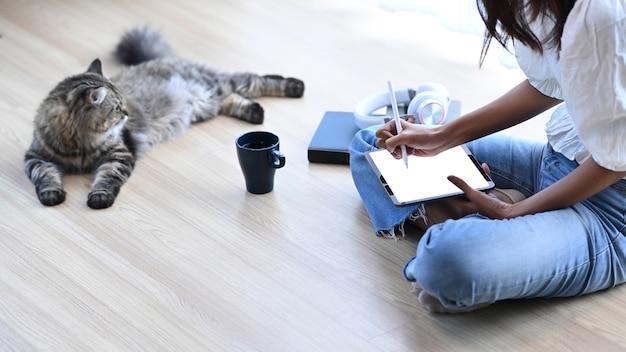 Junge frau, die auf boden mit ihrer katze sitzt und auf digitalem tablett im wohnzimmer zu hause arbeitet.