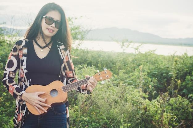 Junge frau, die auf brauner ukulele im park spielt.