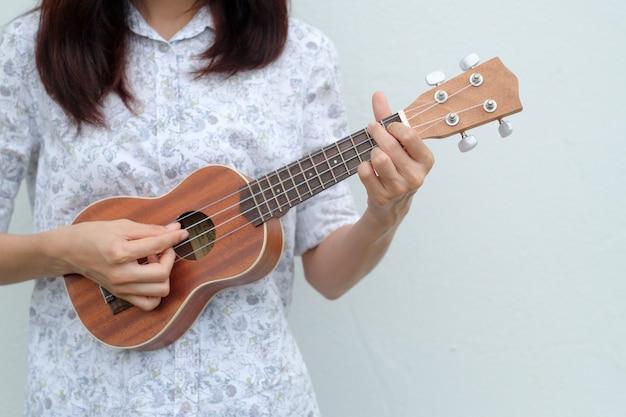 Junge frau, die auf brauner ukulele im weißen oder grauen hintergrund spielt.