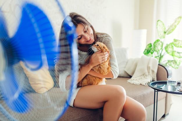 Junge frau, die auf couch durch ventilator zu hause mit katze abkühlt. klimaanlage