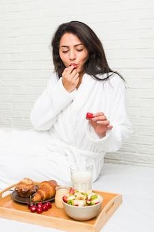 Junge frau, die auf dem bett frühstückt