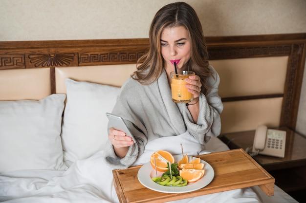 Junge frau, die auf dem bett hat das nahrhafte frühstück betrachtet intelligentes telefon sitzt