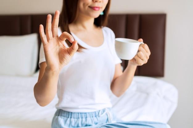 Junge frau, die auf dem bett mit einer tasse kaffee sitzt und ok-zeichen zeigt