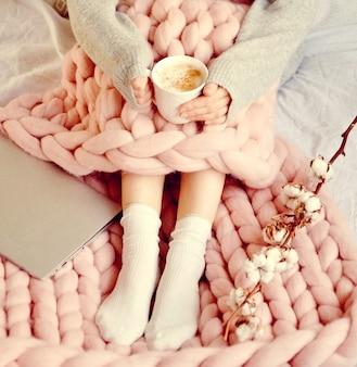 Junge frau, die auf dem bett mit rosa riesiger merino wool plaid-decke mit schale cappuccino sitzt.