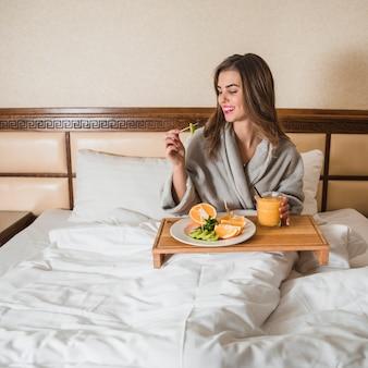 Junge Frau, die auf dem Bett sitzt, das frisch nahrhaftes auf Bett frühstückt