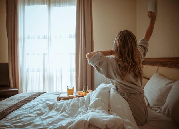 Junge frau, die auf dem bett sitzt, das ihre hand mit frühstück auf tabelle ausdehnt