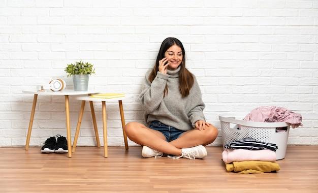 Junge frau, die auf dem boden drinnen mit wäschekorb sitzt und ein gespräch mit dem mobiltelefon mit jemandem hält