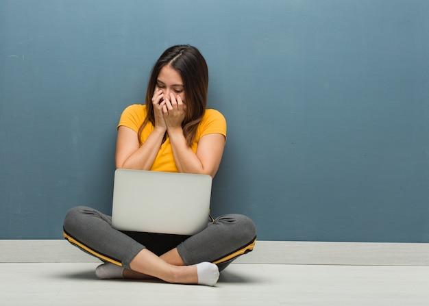 Junge frau, die auf dem boden mit einem laptop lacht über etwas, mund mit den händen bedeckend sitzt