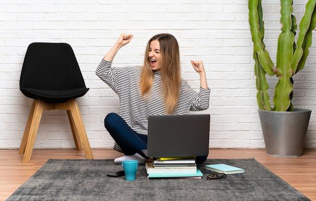 Junge frau, die auf dem boden mit ihrem laptop feiert einen sieg sitzt