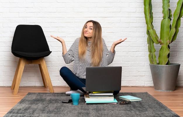 Junge frau, die auf dem boden mit ihrem laptop hat zweifel mit verwirren gesichtsausdruck sitzt