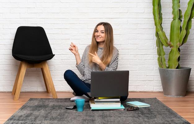 Junge frau, die auf dem boden mit ihrem laptop zeigt finger auf die seite sitzt
