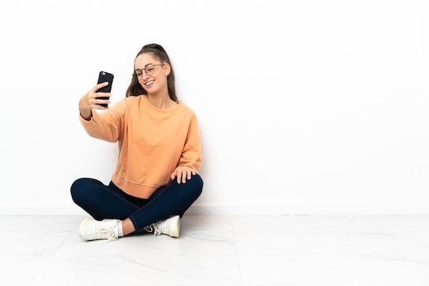 Junge frau, die auf dem boden sitzt und ein selfie macht