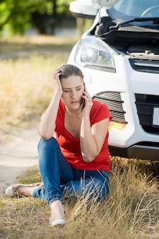 Junge frau, die auf dem boden sitzt und sich auf ein kaputtes auto stützt